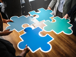 Four people holding a piece of a jigsaw puzzle each